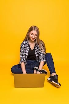 Молодая улыбающаяся женщина сидит на полу с ноутбуком, изолированным на желтой стене