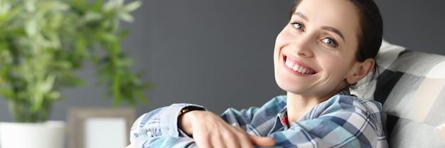 집에서 소파에 앉아 웃고 있는 젊은 여성
