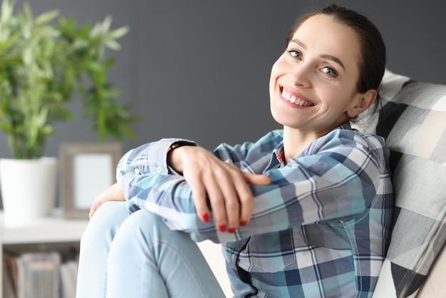 Молодая улыбающаяся женщина, сидящая на диване у себя дома