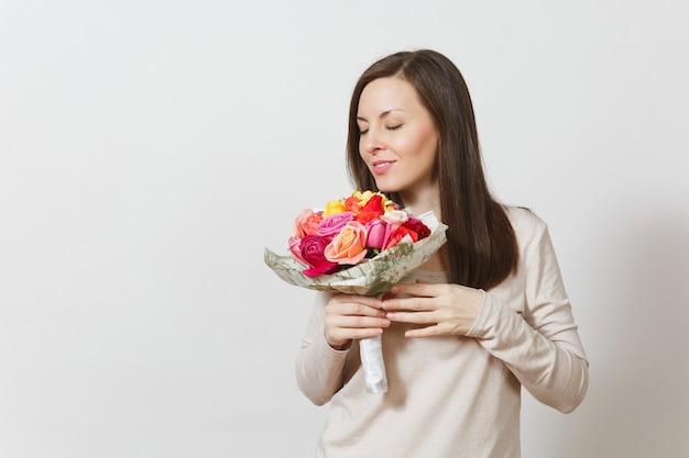 흰색 배경에 격리된 아름다운 장미 꽃다발을 킁킁거리며 들고 웃고 있는 젊은 여성. 광고 공간을 복사합니다. 성 발렌타인 데이 또는 국제 여성의 날 개념.