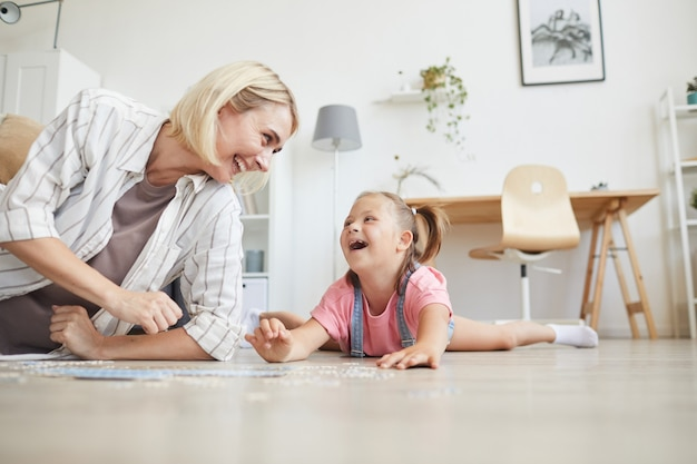 Young smiling woman spending time with her daughter they laughing while lying on the floor and collecting puzzles at home