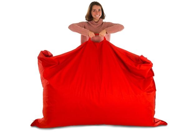 居間または白で隔離される他の部屋のための赤い長方形のビーンバッグソファチェアを立って保持している若い笑顔