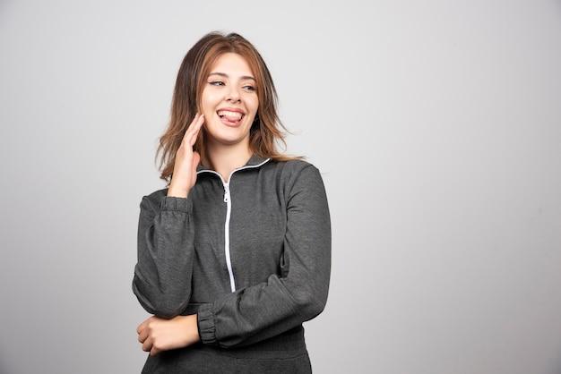 立ってポーズをとって若い笑顔の女性。
