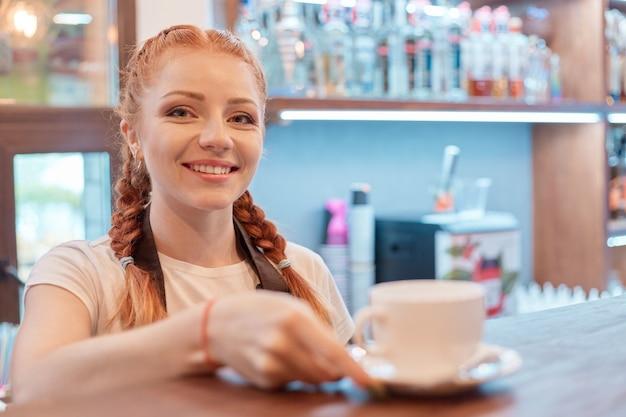 コーヒーショップのバーに立っている若い笑顔の女性
