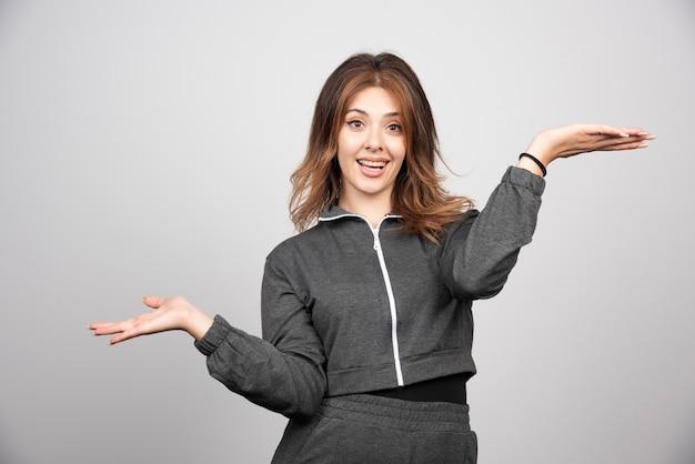 Giovane donna sorridente in piedi e in posa con le mani in alto.