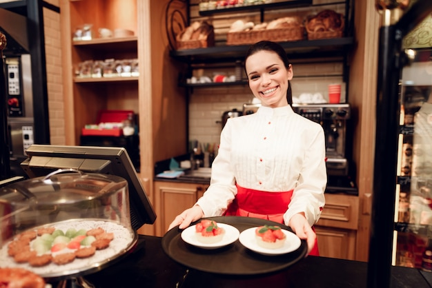 Young smiling woman standing with cakes in bakery.