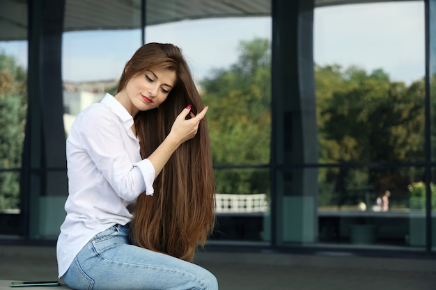 Young smiling woman straightens her long hair