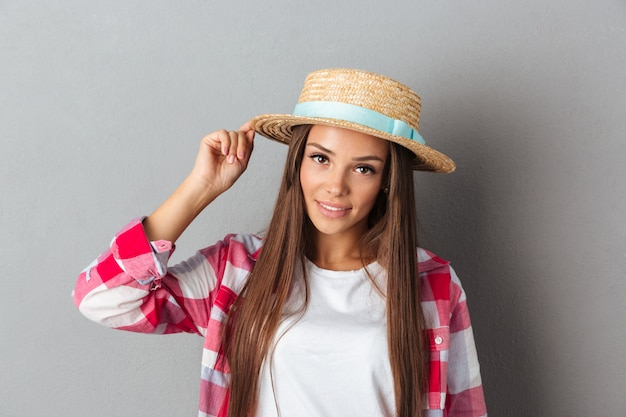 Young smiling woman in straw hat and checkered shirt