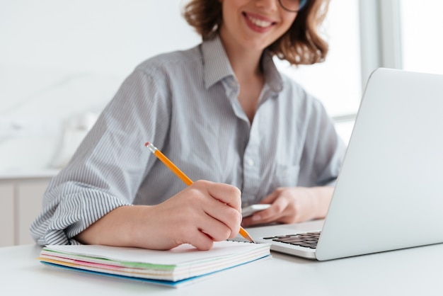 Young smiling woman in striped shirt taking notes while sitting at table in light apartment