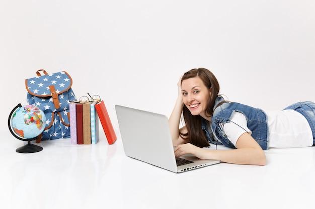 Giovane studentessa sorridente in abiti di jeans che lavora al computer portatile che giace vicino allo zaino del globo e ai libri scolastici isolati