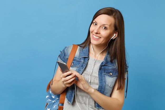 Молодой улыбающийся студент женщины в джинсовой одежде с рюкзаком и наушниками, слушая музыку, держащуюся с помощью мобильного телефона, изолированного на синем фоне. обучение в колледже. скопируйте место для рекламы.