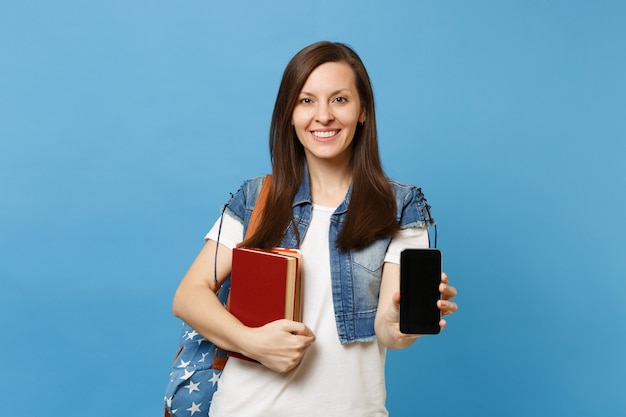 Молодой улыбающийся студент женщины в джинсовой одежде с рюкзаком, держащим школьные учебники, мобильный телефон с пустым черным пустым экраном, изолированным на синем фоне. обучение в средней школе университетского колледжа.