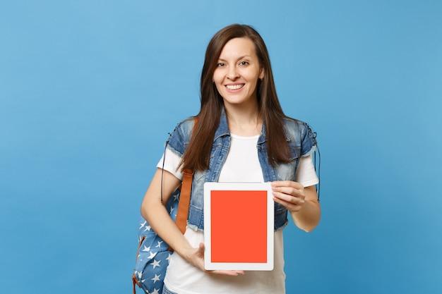파란색 배경에 격리된 빈 검은색 빈 화면이 있는 태블릿 Pc 컴퓨터를 들고 배낭을 메고 데님 옷을 입은 젊은 웃는 여학생. 대학에서 교육입니다. 광고 공간을 복사합니다. 프리미엄 사진