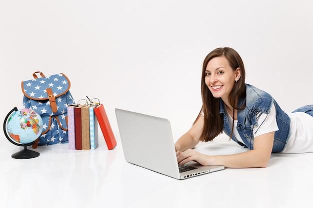 Молодая улыбающаяся студентка в джинсовой одежде, работающая на портативном компьютере, лежащая рядом с рюкзаком глобуса и школьными учебниками