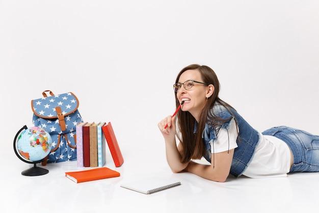 Молодая улыбающаяся женщина-студент в очках думает, грызет и кусает карандаш, лежа рядом с ноутбуком, глобусом, рюкзаком, изолированными школьными учебниками