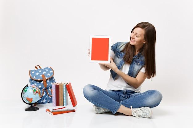 La giovane studentessa sorridente che guarda sul computer tablet pc con schermo vuoto nero vuoto si siede vicino allo zaino del globo, libri di scuola isolati