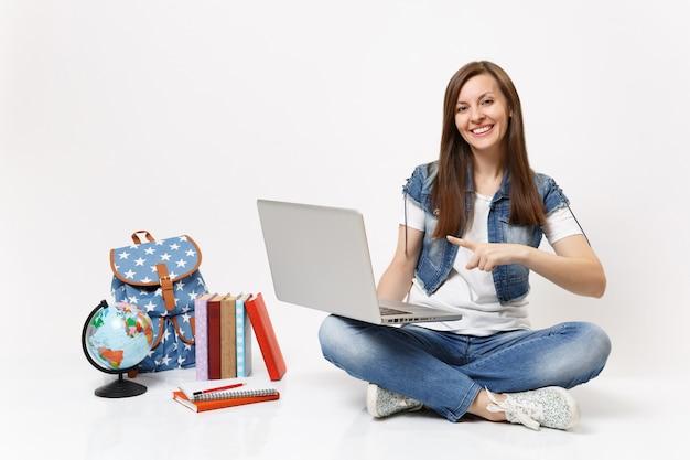 Молодая улыбающаяся женщина-студент, указывая указательным пальцем на портативный компьютер, компьютер, сидя рядом с земным шаром, рюкзаком, школьными учебниками