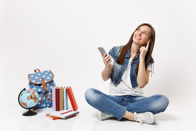 Young smiling woman student with earphones looking up listening music holding mobile phone sitting near globe backpack books isolated