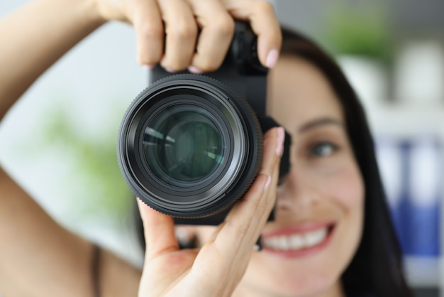 Young smiling woman taking pictures on black professional camera closeup