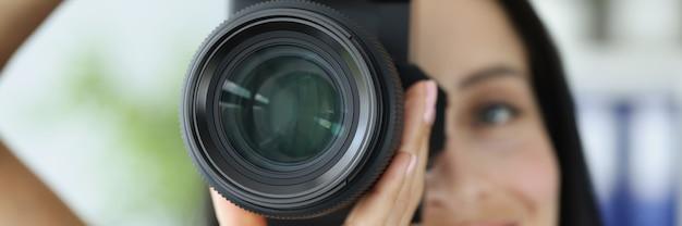 黒のプロのカメラのクローズアップで写真を撮る若い笑顔の女性