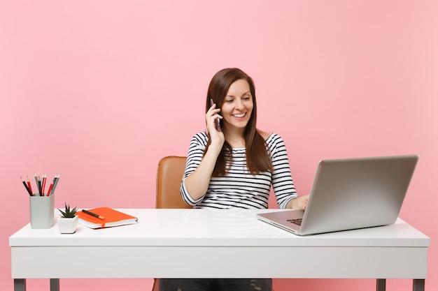 웃고 있는 젊은 여성은 휴대전화로 통화하고 즐거운 대화를 나누며 파스텔 핑크색 배경에 격리된 pc 노트북으로 사무실에서 일합니다. 성취 비즈니스 경력 개념입니다. 공간을 복사합니다.