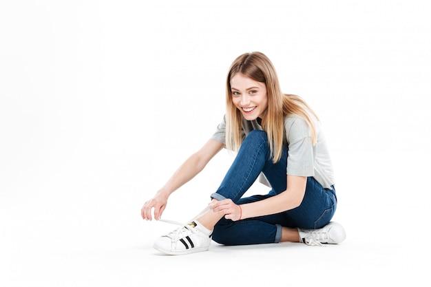 Молодые улыбающиеся женщины завязывают шнурки