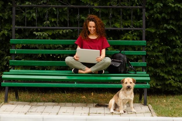 Молодая женщина улыбается, используя свой ноутбук в парке