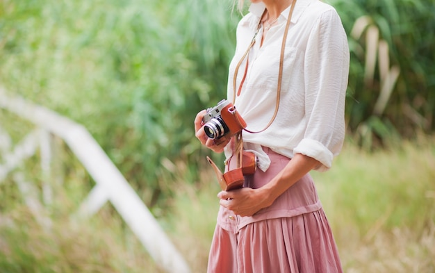 Young smiling woman in vintage style clothes with retro camera