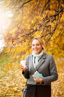Young smiling woman walking and drinking take away coffee in autumn park