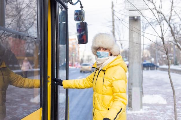 Молодая улыбающаяся женщина заходит в автобус в зимний день