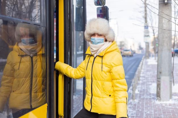 若い笑顔の女性が冬の日にバスに入る