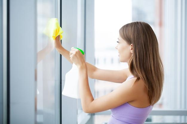 スポンジで窓を洗う若い笑顔の女性
