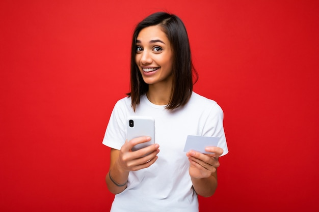 Young smiling woman wearing everyday clothes isolated over background holding phone and credit card paying online shopping through credit card looking at camera