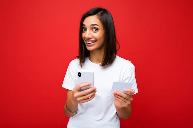 카메라를 보고 신용 카드를 통해 온라인 쇼핑을 지불하는 전화와 신용 카드를 들고 배경 위에 격리된 일상적인 옷을 입고 웃는 젊은 여자