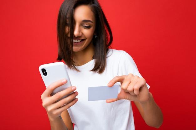 스마트폰 화면을 보고 신용 카드를 통해 온라인 쇼핑을 지불하는 전화와 신용 카드를 들고 배경 위에 고립 된 일상적인 옷을 입고 젊은 웃는 여자.