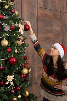 面白い帽子をかぶって、リビングルームの大きなクリスマスツリーに飾りや装飾品をぶら下げてクリスマスを飾る若い笑顔の女性