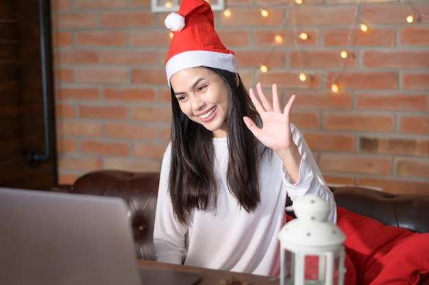 A young smiling woman wearing red santa claus hat making video call on social network with family and friends on christmas day.