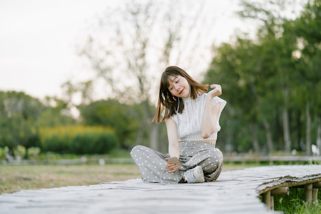 Young smiling woman in white clothes with earphones sitting on wooden walkway in the park and enjoying her moment while using mobile phone listening to music with her eyes looking at the screen