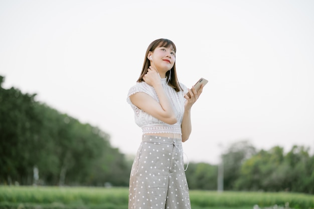 Young smiling woman in white clothes with earphones standing in the park while using mobile phone listening to music with her eyes looking at something interesting in the mood relaxing and happy
