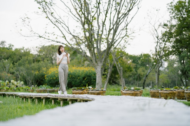 Young smiling woman in white clothes with earphones using mobile phone listening to music with her eyes looking at the screen enjoying her moment while strolling on wooden walkway in the park
