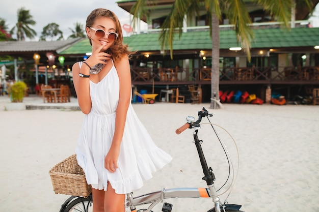 Young smiling woman in white dress riding on tropical beach on bicycle sunglasses traveling on summer vacation in thailand