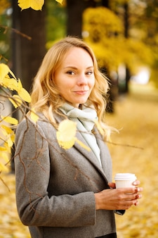 Young smiling woman with coffee outdoors in sunny autumn day closeup portrait looking at camera