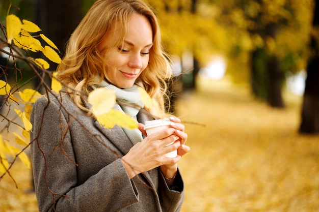 Young smiling woman with coffee outdoors in sunny autumn day closeup portrait with copy space