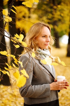 Young smiling woman with coffee outdoors in sunny autumn day closeup portrait