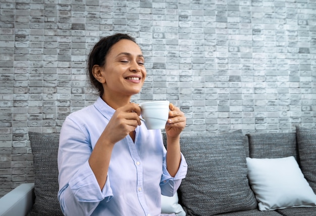The young smiling woman with a cup of coffee in her hands while sitting on the couch.