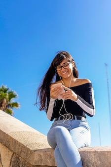 야외에서 앉아있는 동안 안경 휴대 전화로 채팅 젊은 웃는 여자