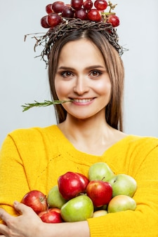 Young smiling woman with fruit. a beautiful brunette in a yellow sweater with purple grapes on her head