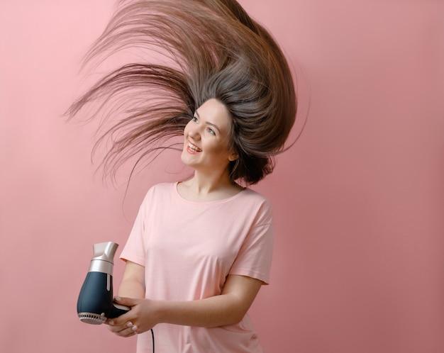 ピンクの背景の強い風の髪の飛行の手にヘアドライヤーと若い笑顔の女性