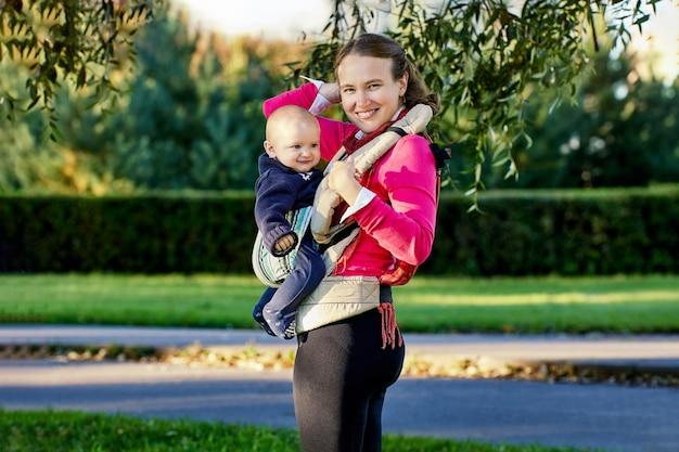 Молодая улыбающаяся женщина с младенцем в детской слинге гуляет в парке во время декретного отпуска.