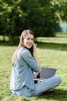 푸른 잔디와 풀밭에 앉아 노트북으로 젊은 웃는 여자